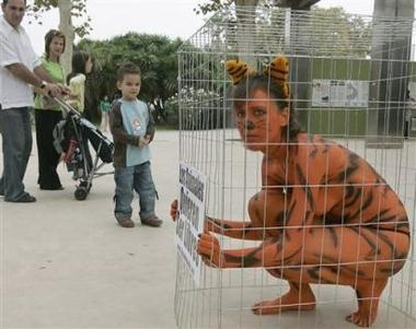 A protester from PETA , People for the Ethical Treatment of Animals crouches in a cage outside the Zoo in Barcelona, Spain Sunday Sept. 25, 2005. The protest was to highlight the plight of wild animals kept in cages in zoos, whom activists say are deprived of their natural environment. (AP Photo/Manu Fernandez)