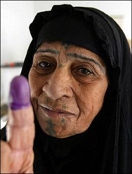 An Iraqi woman shows her ink-stained finger after voting at polling station in Baghdad's Sadr city neighborhood. Iraqis voted in force on a draft constitution that turns another page on the ousted regime of Saddam Hussein amid a general calm.(AFP/Ahmad al-Rubaye)
