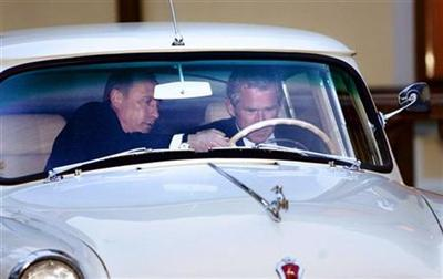 President Bush and Russian President Vladimir Putin climb into a vintage 1956 Volga to drive to dinner within Putin's private residence compound Odinsovsky just outside Moscow Sunday, May 8, 2005. 'Be careful',Bush joshed to reporters. He's giving me a driving lesson.'(AP Photo/Gerald Herbert).