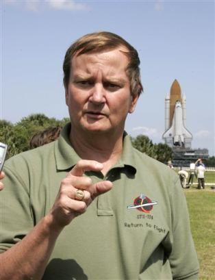 Shuttle launch director Mike Leinbach chats with the media as space shuttle Discovery, right, slowly moves towards the pad at Kennedy Space Center in Cape Canaveral, Fla,Wednesday, Apr. 6, 2005. Discovery is scheduled for launch no earlier than May 15 on a mission to the international space station carrying a crew of seven.(AP Photo/Terry Renna)