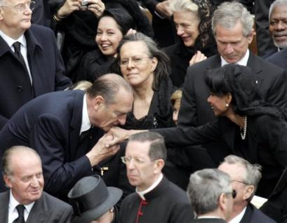 S President George Bush looks on as French President Jacques Chirac kisses the hand of Secretary of State Condoleezza Rice, and former US President Bill Clinton looks the other way, second from top right, after the funeral mass for Pope John Paul II in St. Peter's Square at the Vatican, Friday, April 8, 2005. Sitting looking at Chirac kissing Rice's hand is First Lady Laura Bush. At bottom left, is King Juan Carlos of Spain and Queen Sofia with black hat; at top left, UN Secretary General Kofi Annan. In background behind President Bush, Palestinian Qureia, widely known as Abu Ala (AP Photo/Andrew Medichini)
