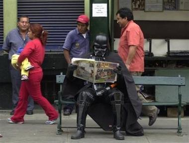 Hugo Casachahua, dressed as Darth Vader, one of the main characters in the Star Wars saga, reads a newspaper while waiting for the premiere of 'Star Wars: Episode III - Revenge of the Sith' in Lima, Peru Wednesday, May 18, 2005. (AP Photo/Karel Navarro)