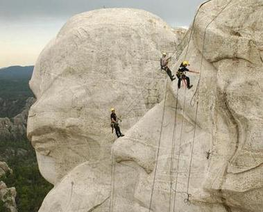 Knut Foppe, left, Darin Oestmann, center, with the National Park Service and Thorsten Mowes, right, rappel a sculpture of Thomas Jefferson's face to begin power washing Mount Rushmore National Monument, Thursday, July 7, 2005, near Keystone, S.D. (AP Photo/Doug Dreyer)