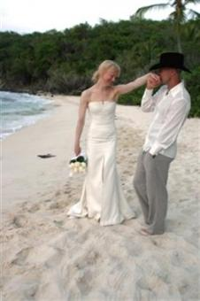 This photo from Carolina Herrera shows country music star Kenny Chesney kissing the hand of his bride, actress Renee Zellweger, wearing her Carolina Herrera designed wedding dress, on the beach in Cruz Bay, on St.John in the U.S. Virgin Islands on Monday, May 9, 2005. (AP Photo/Carolina Herrera)