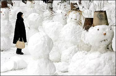 Many a snowman : A woman looks at snowmen installed at the Arbat, a popular pedestrian shopping and entertainment street in Moscow. (AFP/Denis Sinyakov)