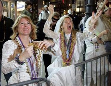 Sisters Lynn Martin from Bowling Green, KY, left, Lisa Lander from Narrowsburg, NY and their mother Flo Billard also of Narrowsburg dress as brides to help get attention to catch more beads at the parades during the Mardi Gras season in New Orleans on Thursday Feb. 23, 2006. (AP Photo/Alex Brandon)