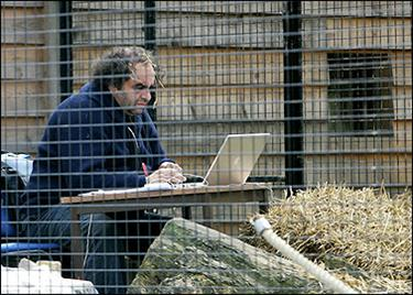 Playwright Norbert Aboudarham, writes his play on a laptop while sitting in a cage at the Amiens zoo 13 April 2006. Aboudarham, in search of inspiration for
