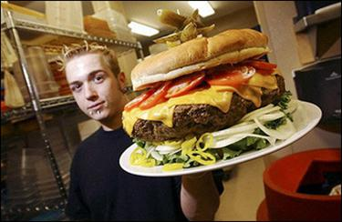 Chef Jeff Zellner of Denny's Beer Barrell hoists one of the establishment's record-breaking burgers in the kitchen in Clearfield, Pennsylvania, in May 2005. European lawmakers adopted new laws on food labels aimed at fighting obesity by ensuring that consumers are warned about high levels of sugar, fat and salt in products.(AFP/Getty Images/File/Jeff Swensen)