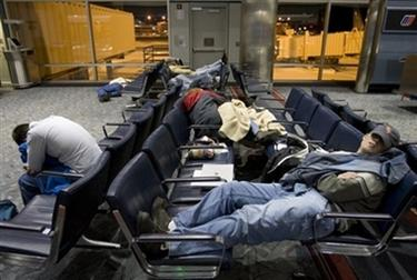 Passengers sleep in Concourse B on Thursday night, Dec. 21, 2006, at Denver International Airport in Denver. Nearly 5,000 air passengers who got stuck at Denver International Airport spent another frustrating day trying to forge through a snowbound city to hotels--or opting to bed down again in the terminal. The airport wasn't expected to reopen until noon Friday. (AP Photo/Will Powers)