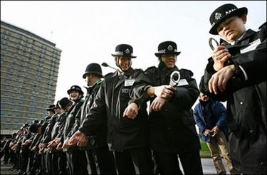 Some 305 British Metropolitan Police recruits and staff members handcuff themselves together as part of a world record attempt for the most amount of people handcuffed in a chain at the police training academy in Hendon, north London.(AFP/Adrian Dennis)
