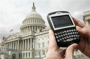 A journalist looks at her Blackberry communication device on Capitol Hill in Washington, April 18, 2007. Research In Motion Ltd. said on Thursday the full analysis of the cause of the North American outage of its BlackBerry e-mail service 'will take more time,' but the company expected to have an update by Friday morning. (Jim Young/Reuters)
