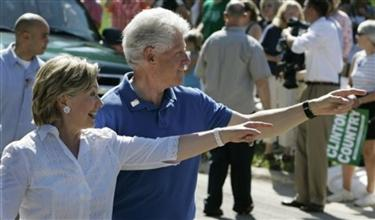 Democratic presidential hopeful U.S. Sen. Hillary Rodham Clinton, D-N.Y., and her husband, former President Bill Clinton, point to supporters as they walk in the Fourth of July Parade Wednesday, July 4, 2007 in Clear Lake, Iowa. (AP Photo/M. Spencer Green)