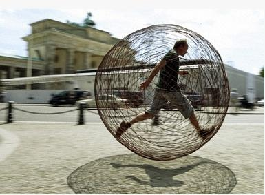 Drossel runs : Artist Arnd Drossel runs past Berlin's landmark Brandenburg Gate in his sphere made of steel wire which he hopes to run in from Berlin to the western German town of Paderborn to raise support for the 'social psychiatric' initative in Padrborn.(AFP/DDP/Axel Schmidt)