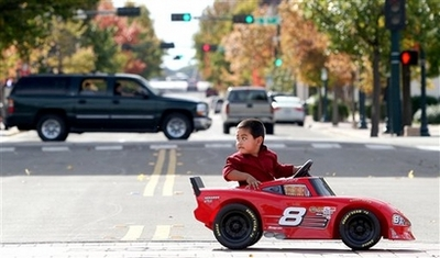 Hugh DeLaRosa, 3, looks over his shoulder, Monday, Dec. 3, 2007, as he drives his motorized toy stock car across a downtown street in Waco, Texas, while his parents, not pictured, walk just ahead of him. (AP Photo/The Waco Tribune-Herald, Jerry Larson)