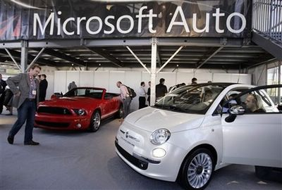 Attendees look at a Fiat, right, and Ford Cobra, left, at the Microsoft Auto exhibit at the Consumer Electronics Show (CES) in Las Vegas, Monday, Jan. 7, 2008. (AP Photo/Paul Sakuma)