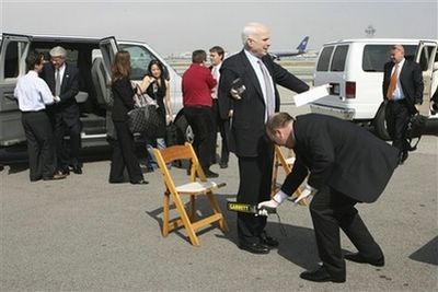Republican presidential candidate, Sen. John McCain, R-Ariz., left is is checked by security personnel prior to boarding an airplane, Wednesday, March 26, 2008, in Los Angeles. (AP Photo/Mary Altaffer)