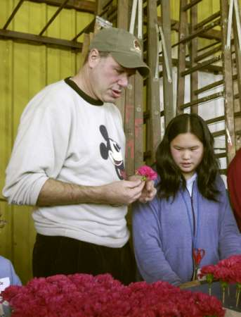 Walt Disney Company Chairman and CEO Michael Eisner and volunteer Jennifer Yuen, 13 of Rosemead, California help to prepare flowers for Disney's Tournament of Roses Twilight Zone Tower of Terror float in Pasadena, California, December 30, 2003. The float will be in the Tournament of Roses Parade in Pasadena, California January 1, 2004. The Twilight Zone Tower of Terror will be the newest attraction to open at Disney's California Adventure in 2004. FOR EDITORIAL USE ONLY NO SALES REUTERS/Adrienne Helitzer/Disney/Handout
