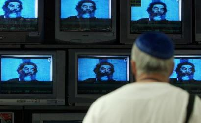 An Israeli man in a electric appliances store in Tel Aviv, Israel watches TV sets showing footage of a live broadcast of a news conference from Baghdad, Iraq announcing Saddam Hussein's capture Sunday, Dec. 14, 2003. U.S. administrator L. Paul Bremer said Saddam Hussein was captured near his hometown of Tikrit. (AP Photo/Ariel Schalit)