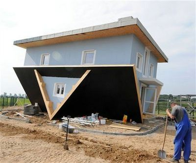 A worker stands in front of the 'Upside Down House' in Trassenheide on Usedom Island, northern Germany, Tuesday, Aug. 26, 2008. The house of an entrepreneur from Poland is part of the project 'The World Upside Down' that should allow visitors a different view of every day items. The building is expected to open its doors for visitors in the upcoming week. (AP Photo/Frank Hormann)