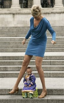 He Pingping from Inner Mongolia, China's autonomous region, the world's smallest man sits underneath Svetlana Pankratova from Russia, the Queen of Longest Legs, as they pose at Trafalgar Square in London, Tuesday, Sept. 16, 2008. Pingping, born with primordial dwarfism, holds the Guinness World Record for the smallest man at 74.61 cms (2 feet and 5.37 inches) and Pankratova holds the Guinness World Record for the longest leg of any woman at 132 cms (4 feet 4 inches) in length. (AP Photo/Sang Tan)