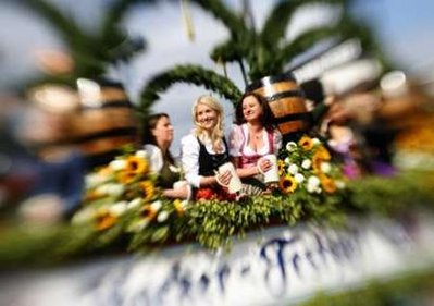 Bavarian women smile from a horse drawn carriage during the Oktoberfest parade in Munich September 20, 2008. Millions of beer drinkers from around the world come to the Bavarian capital Munich for the world's bigest and most famous beer festival, the Oktoberfest. The 175th Oktoberfest lasts until October 5.Picture taken with a tilt lens. REUTERS/Pawel Kopczynski (GERMANY)