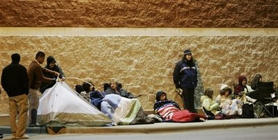 Shoppers prepare for a long night waiting outside an electronics store in Lawrence, Kan., Thursday, Nov. 27, 2008. The campers hope to take advantage of early bird shopping specials when the electronics department store opens it's doors Friday. (AP Photo/Orlin Wagner)