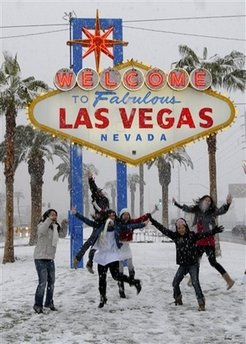 In this photo provided by the Las Vegas News Bureau, people play in the snow in front of the Las Vegas welcome sign in Las Vegas on Wednesday, Dec. 17, 2008. (AP Photo/Las Vegas News Bureau, Darrin Bush)