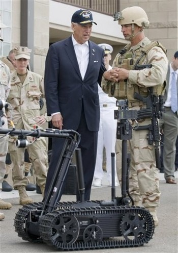 Vice President Joe Biden, center, talks with Navy sailor Ken Englehart, right, as they watch a demonstration of a Talon robot during a visit to the Naval Amphibious Base Coronado in Coronado, Calif. Thursday, May 14, 2009. The robot is used to dismantle explosive devices.