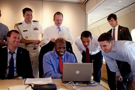 President Barack Obama and White House staffers aboard Air Force One to Paris look at Reggie Love's photos of Egypt on June 5, 2009 (Official White House photo by Pete Souza)