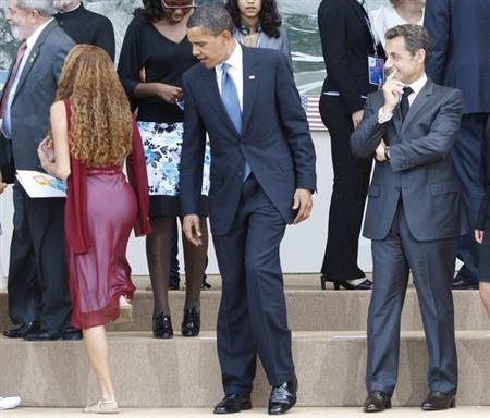 U.S. President Barack Obama (C) and France's President Nicolas Sarkozy (R) take their places with junior G8 delegates for a family photo at the G8 summit in L'Aquila, Italy, July 9, 2009. Leaders of the Group of Eight major industrial nations and the main developing economies are meeting in the central Italian city of L'Aquila until Friday to discuss issues ranging from global economic stimulus to climate change and oil prices. REUTERS/Jason Reed (ITALY POLITICS IMAGES OF THE DAY)