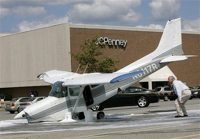 An investigator looks at a plane that crash-landed in a parking lot at the Rockaway Townsquare Mall in Rockaway Township, N.J., Tuesday, Aug. 25, 2009. The small plane made an emergency landing in the mall, slightly injuring the instructor and student inside but apparently hurting no one on the ground. (AP Photo/Rich Schultz)
