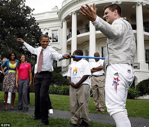 En garde: Mr Obama jabs Olympic Champion Tom Morehouse with First Lady Michelle Obama behind him