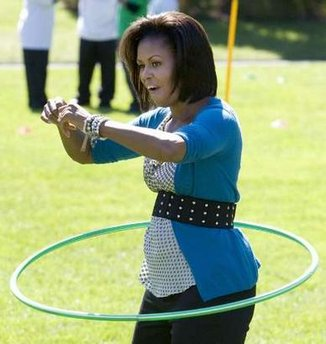U.S. first lady Michelle Obama hula hoops with kids at the White House Healthy Kids Fair on the South Lawn in Washington, October 21, 2009. REUTERS/Larry Downing (UNITED STATES POLITICS IMAGES OF THE DAY)