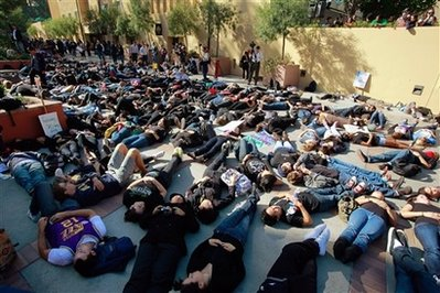 Hundreds of students lay down to symbolize the 'Death of Public Education,' as they protest peacefully outside the UCLA campus Covel Commons building, where University of California regents were scheduled to vote on a 32 percent student fee increase, on Thursday, Nov. 19, 2009. The UC Board of Regents is considering boosting undergraduate fees, the equivalent of tuition, by $2,500 by summer 2010.<br /> (AP Photo/Damian Dovarganes)