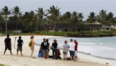 Members of the media and onlookers stand on the beach near where President Barack Obama, first lady Michelle Obama, and daughters Sasha and Malia are having their holiday vacation in Kailua, Hawaii., Thursday, Dec. 24, 2009. (AP Photo/Chris Carlson)