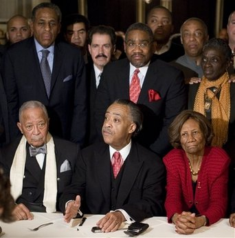Former New York City Mayor David Dinkins, left, and NAACP official Hazel Dukes, right, sit next to Rev. Al Sharpton, center, as he address the media after meeting with the local political base to discuss the future political life of New York State Governor David Patterson Thursday, March 4, 2010 in the Harlem neighborhood of New York. State and local politicians, and community leaders who attended the meeting stand behind Sharpton. (AP Photo/Stephen Chernin)