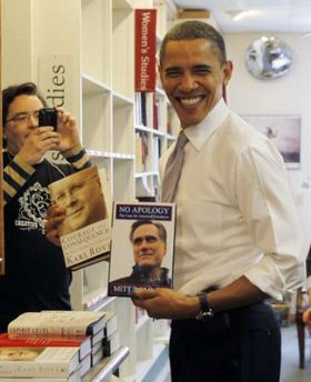U.S. President Barack Obama holds up books by former Republican presidential candidate Mitt Romney and President George W. Bush's political strategist Karl Rove (L) as he shops for books for his daughters Sasha and Malia at Prairie Lights book store in Iowa City, March 25, 2010. REUTERS/Jason Reed (UNITED STATES - Tags: POLITICS)