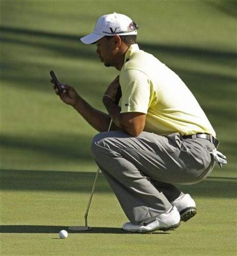 Tiger Woods checks his cell phone during a practice round at the Masters golf tournament in Augusta, Ga. , Tuesday, April 6, 2010.
