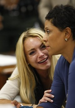 Actress Lindsay Lohan, left, reacts with her attorney Shawn Chapman Holley after the sentencing by Superior Court Judge Marsha Reve during a hearing in Beverly Hills, Calif., Tuesday, July 6, 2010. The judge sentenced Lindsay Lohan to 90 days in jail Tuesday after ruling she violated probation in a 2007 drug case by failing to attend court-ordered alcohol education classes. (AP Photo/David McNew)