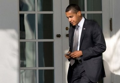 US President Barack Obama uses his BlackBerry or similar device as he walks to the Oval Office in Washington, DC in 2009. Obama fought hard to keep his BlackBerry when he became president, but with only 10 people authorized to email the super-encrypted device, he admitted Thursday that it is 'no fun.'(AFP/File/Saul Loeb)