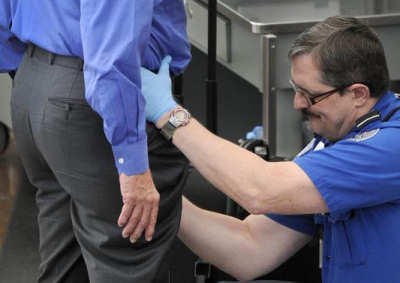 A TSA employee conducts one the new enhanced searches