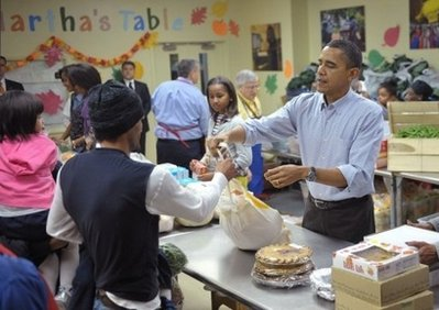 President Barack Obama distributes food at Martha?s Table, a charity providing food and shelter to poor people, a day before Thanksgiving. Obama has saidthe United States is 'hurting' as he used a Thanksgiving address to call for support for US troops and cooperation from his rivals in a divided Washington.(AFP/Mandel Ngan)