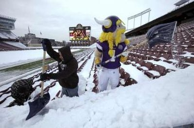Viktor, the Minnesota Vikings mascot, helps remove snow from the seats in the TCF Bank Stadium football field at the University of Minnesota football field in Minneapolis, December 15, 2010. The Vikings are scheduled to play the Chicago Bears at the outdoor stadium after snow collapsed the roof of the Metrodome, the Vikings' home field. REUTERS/Eric Miller <br />