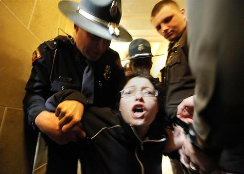 Elizabeth Wrigley-Field is escorted out of the Wisconsin State Capitol Assembly Room lobby Thursday, March 10, 2011 by law enforcement personnel after spending the night in the room with demonstrations opposed to Governor Scott Walker's budget repair bill. Tensions have flared after Republican senators passed an amended version of the controversial bill which largely strips collective bargaining for public employees. (John Hart - State Journal.)