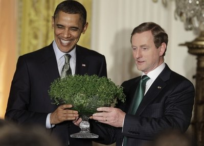 President Barack Obama receives a bowl of shamrock from Prime Minister Enda Kenny of Ireland at a St. Patrick's Day celebration in the East Room of the White House in Washington, Thursday, March 17, 2011. (AP Photo)
