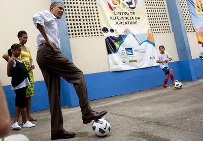 US President Barack Obama plays soccer with some children while visiting Ciudad de Dues Favela in Rio de Janiero, Brazil. Obama visited a notorious favela in Rio de Janeiro Sunday as he visited emerging economic powerhouse Brazil on the first stop on a three-nation Latin America tour. (AFP/Jim Watson)