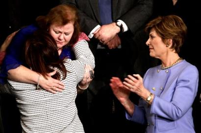 First lady Laura Bush, right, applauds as Safia Taleb al-Suhail, leader of the Iraqi Women's Political Council, back to camera, hugs Janet Norwood of Pflugerville, Texas, on Capitol Hill Wednesday, Feb. 2., 2005 during President Bush's State of the Union address. Mrs.Norwood's son Sgt. Byron Norwood was killed in Iraq last Nov. (AP Photo/Gerald Herbert)