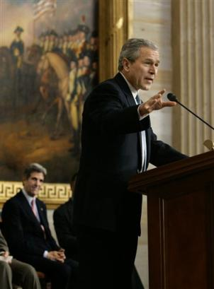 In the rotunda of the U.S. Capitol, President Bush pays tribute to the late baseball legend Jackie Robinson, the first black baseball player to break major league baseball's racial barrier by joining the Brooklyn Dodgers in 1947, in Washington, Wednesday, March 2, 2005. Bush's former rival in the 2004 presidential race, Sen. John Kerry, D-Mass., the sponsor of the legislation to honor Robinson, listens at left. Robinson's widow, Rachel, accepted the Congressional Gold Medal in honor of Robinson's achievements on and off the baseball diamond. (AP Photo/J. Scott Applewhite)