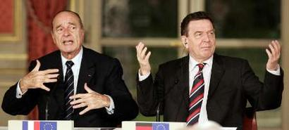 German Chancellor Gerhard Schroeder (R) signals for the translation as French President Jacques Chirac makes opening remarks at a joint press conference at the Elysee Palace in Paris, March 18, 2005. Chirac met with Schroeder, Spanish Prime Minister Jose Luis Rodriguez Zapatero, and Russian President Vladimir Putin for informal talks about relations between the European Union and Russia. REUTERS/John Schults