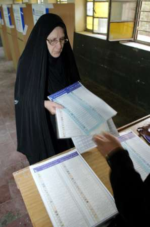 An Iraqi woman receives ballot papers at al-Kadhmiya polling station in Baghdad, January 30, 2005. REUTERS/Thaier Al-Sudani